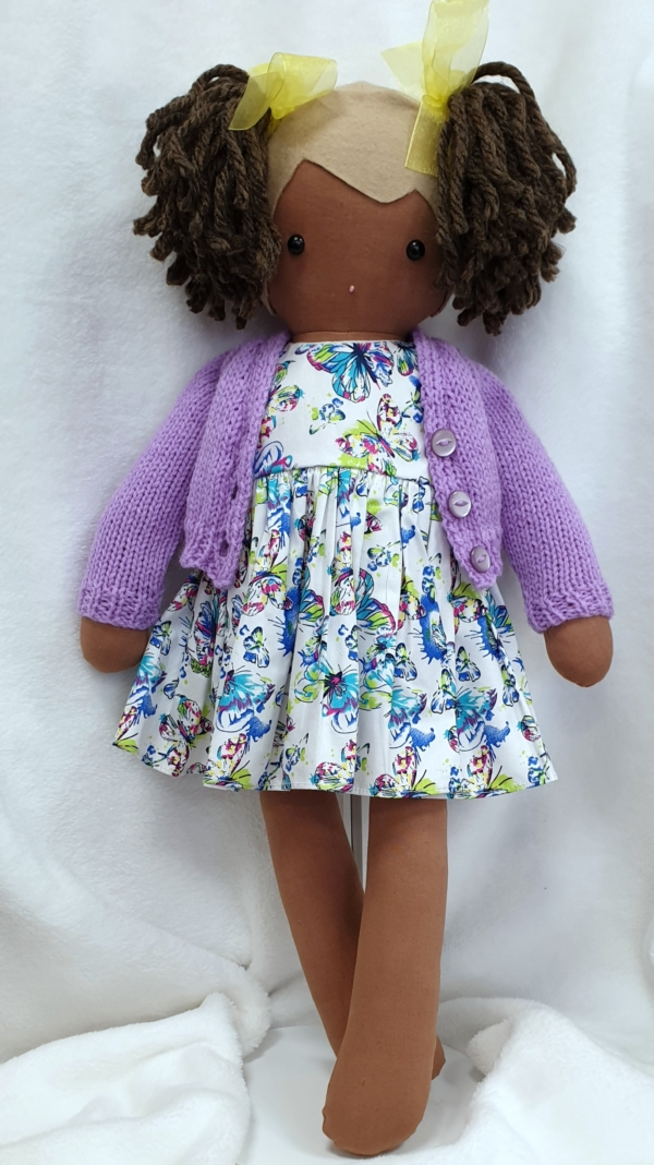 Brown Kornwell Kidz girl rag doll wearing a dress with a butterfly design. She has sand felt and brown bunches
