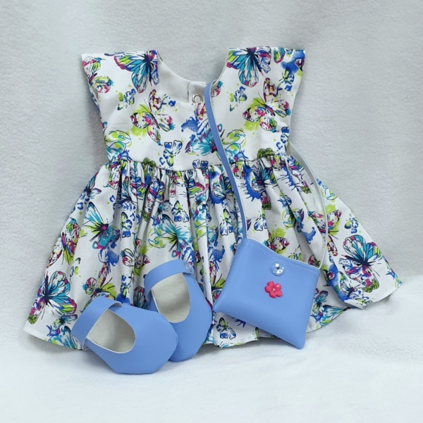 White dress with multicoloured butterflies combined with cornflower blue handbag and shoes